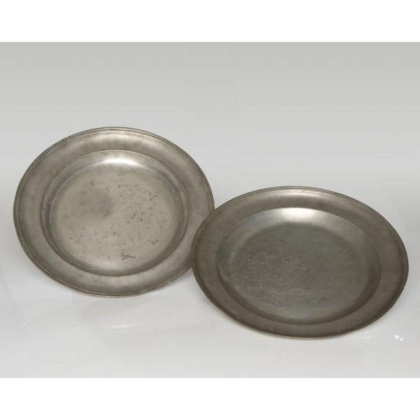 A pair of large pewter chargers from England c. 1820 each having a rolled rim with a sloped edge leading to a shallow...