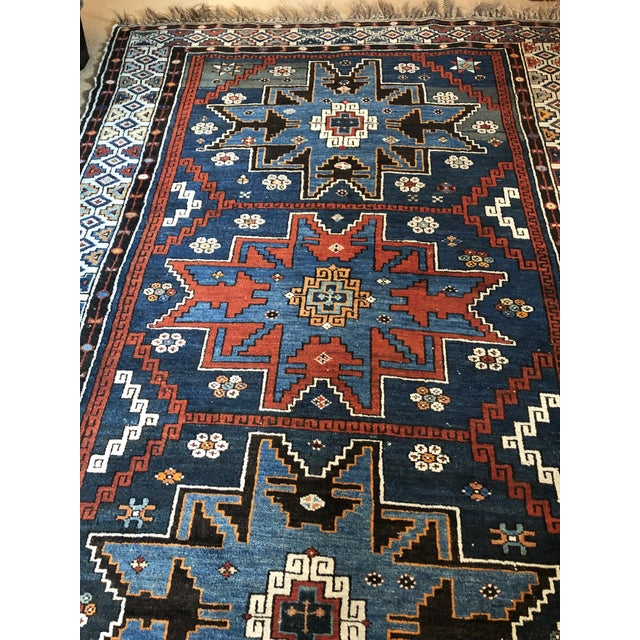 A beautifully patterned antique area rug having geometric designs in navy blue, light blue, cranberry and white.