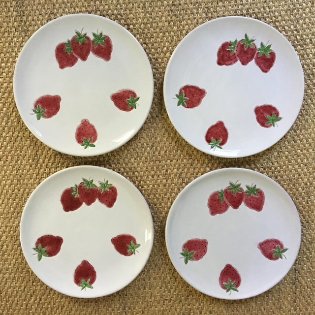 This is a set of four plates made in Italy and embellished with six red strawberries on a white background. Each plate is...
