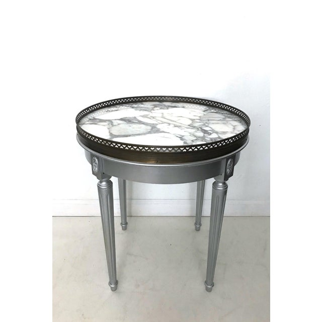 Vintage accent or side/drinks table with a crisp gray and white marble top, surrounded by a finely cast brass gallery....