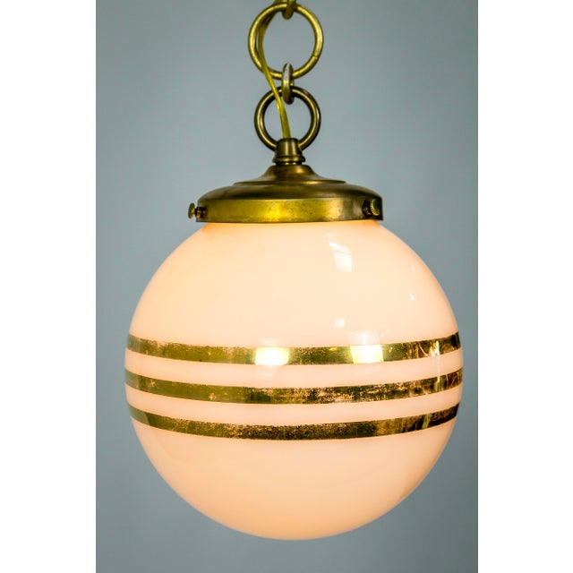This pair of 1960's American white glass globes with 14 carat gold stripes have been newly made into pendants; with and...