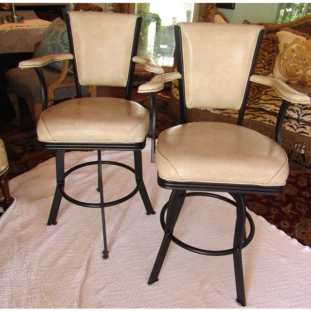 Pair of Iron bar stools. These feature faux leather upholstery in a light brown/ dark cream, a circular foot rest,...