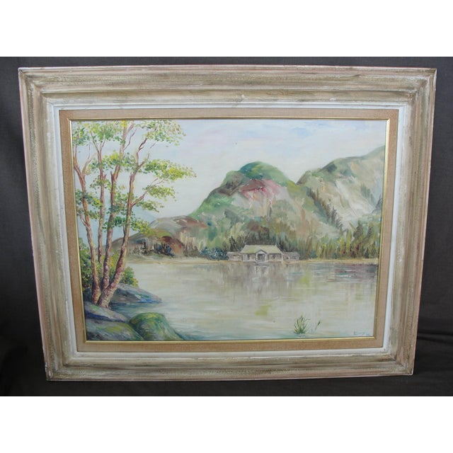This is a oil painting on board of a cabin on a mountain lake. The painting is done in the impressionist manner and is...