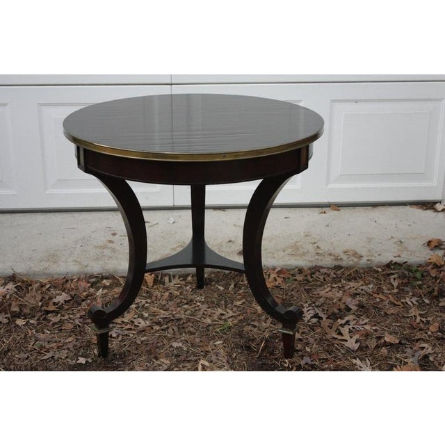 Stunning round mahogany table with narrow brass lip detail. Interesting and whimsical curled legs that have an abrupt...