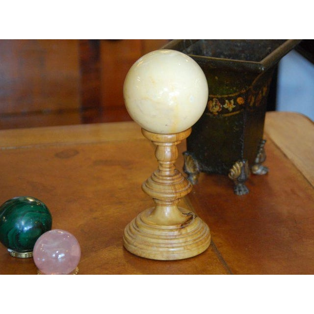 Offering a marble sphere on wooden pedestal.