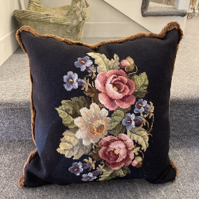 This is a beautiful needle point pillow with a floral design with fringe. The back is plaid.