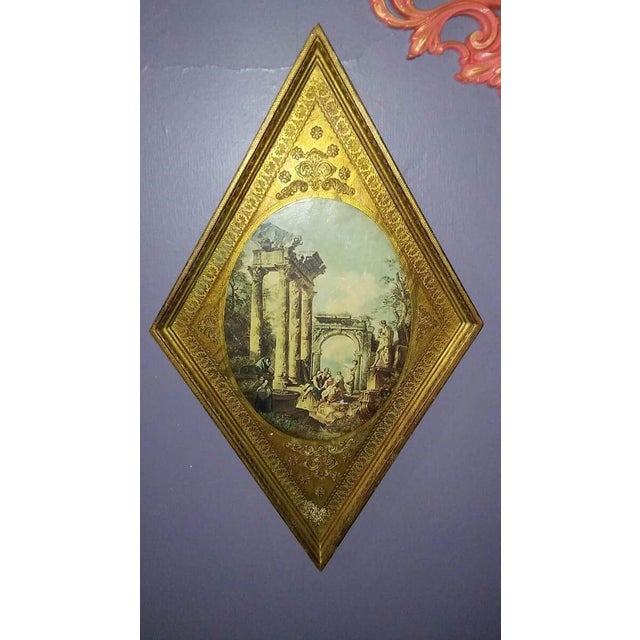 Vintage Italian wood tole wall hanging. Lovely gold gilt framed center print of Roman or Grecian scene. This item has some...