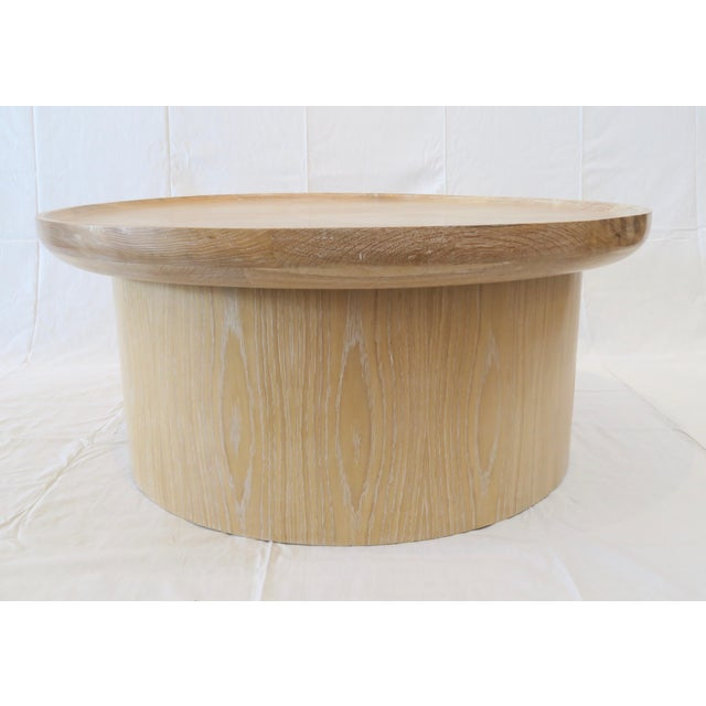 Round Coffee table in Cerused Oak finish. Raised lip detail around edge.