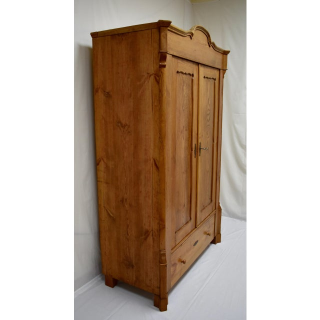 This is an extremely sturdy and well-built pitch pine armoire. Beneath a nicely-scalloped crown molding and plain frieze...