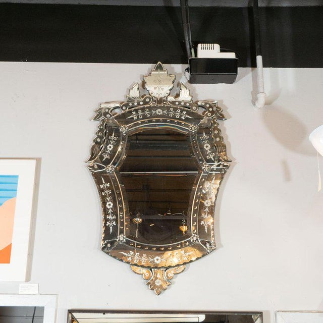 This glamorous mirror was realized in Italy, circa 1950. It offers a cartouche form with mirrored forms resembling...