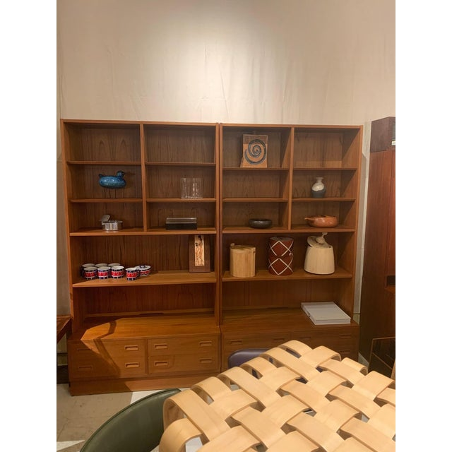 A versatile pair of teak bookcases with five adjustable shelves and one fixed shelf. Each base consists of four drawers...