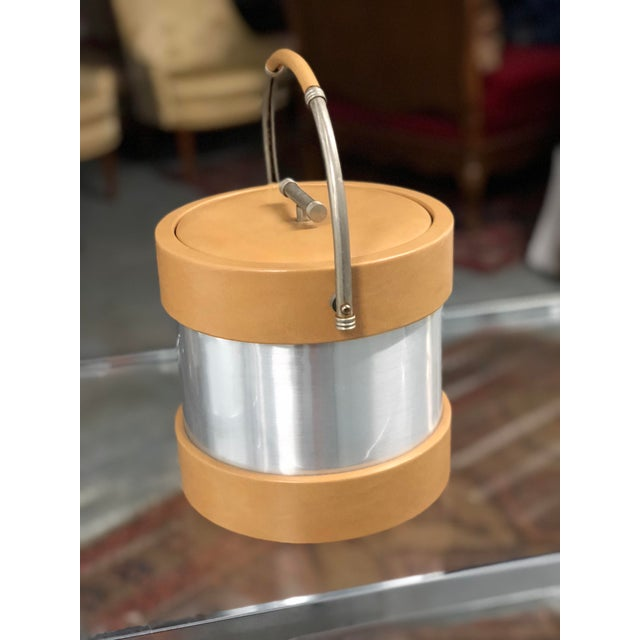 """Retro ice bucket made of camel colored vinyl and chrome with a matching handle and lid. Marked underneath """"Barware by..."""