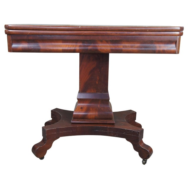 Exceptional flame mahogany game table, circa 1850s. Features a solid mahogany swivel flip top with compartments beneith...