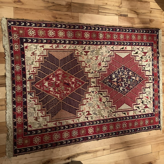 This is an antique silk Sumac Persian rug. The piece dates back to the late 19th century.