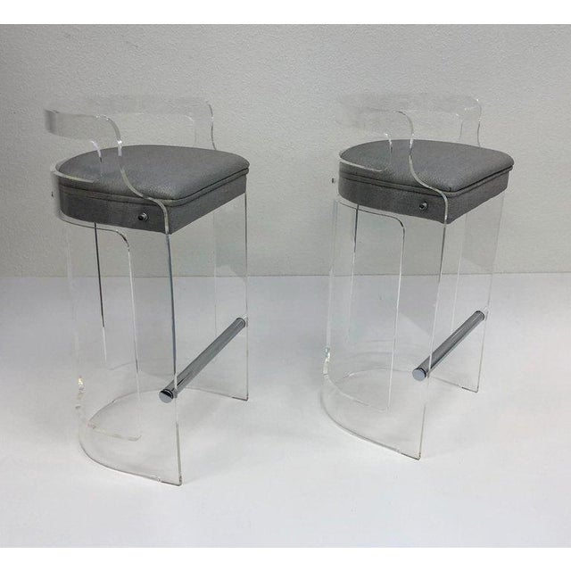 A glamorous pair of clear acrylic and polish chrome barstools design in the 1980s by Hill Manufacturing Co. The seat is...