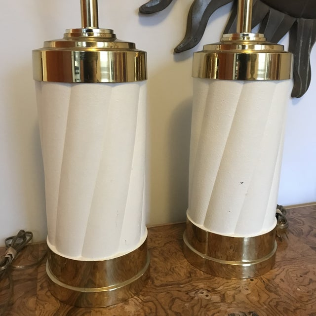 Fabulous pair of 1980's art deco lamps in solid brass with cream spiraled enameled center portion. Harps and finials...