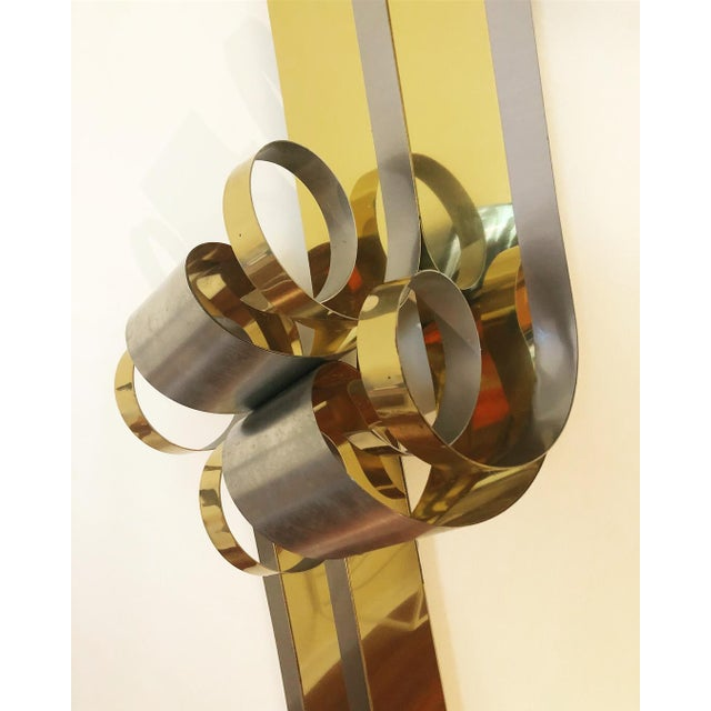 Beautiful fluid sculpture. Can be hung in any orientation. Shows light patina and signs of age to brushed steel and brass.