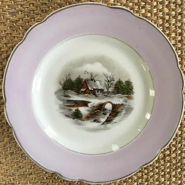 Decorative set of four scalloped porcelain plates with gold trim. Each plate has a different colored rim and a different...
