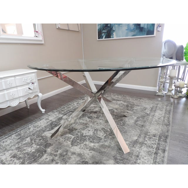 Modern round glass top table with polished chrome base. This 54 inch dining table adds sophisticated style to an interior...
