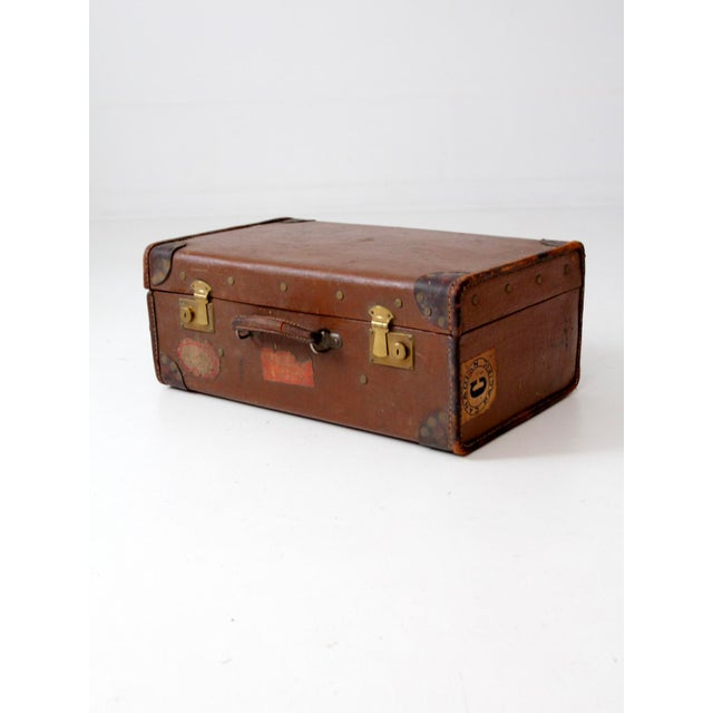 A vintage suitcase with travel stickers. The brown hard case luggage features leather corners and a leather handle. Brass...