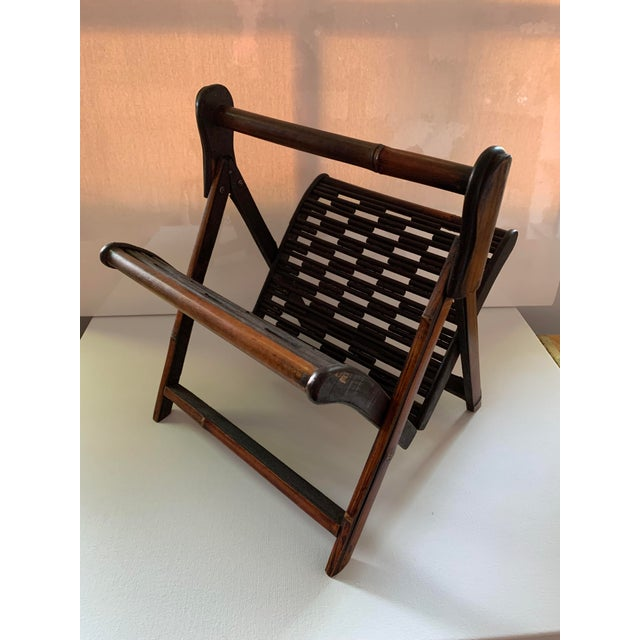Folding magazine rack with burnished bamboo handle and legs. Folds easily when picked up by the handle for carrying.