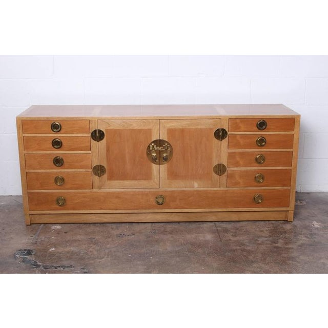 A bleached mahogany sideboard with brass hardware and removable glass tray. Designed by Edward Wormley for Dunbar.