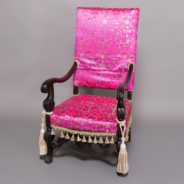 An antique English Elizabethan style throne chair offers mahogany construction with high back, carved scroll arms with...