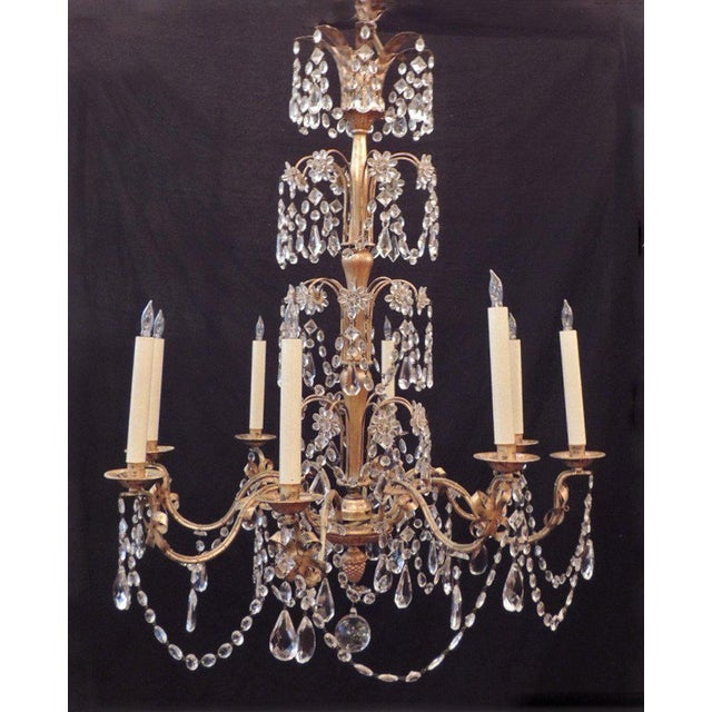 This chandelier was made in France during the mid-20th century, circa 1950. This piece features three tiers of crystal...