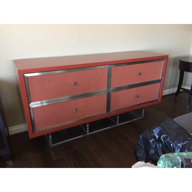Custom credenza with a clear Lucite base and a burnt red lacquer wood frame (satin finish). Drawer fronts are covered in...