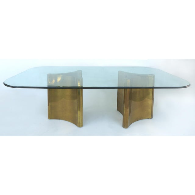 "Offered for sale is a Mastercraft brass ""Trilobi"" double pedestal dining table with an o-gee bull nose beveled glass top...."
