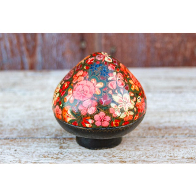 This lovely decorative teardrop shaped paper-mache box designed with a myriad of blossoming flowers hand-painted upon a...