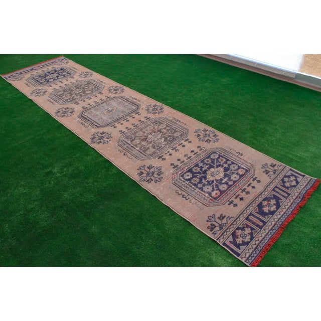 Vintage 1950s distressed Turkish Oushak rug runner. with salmon field and shades of ivory, green,blue and dark blue...