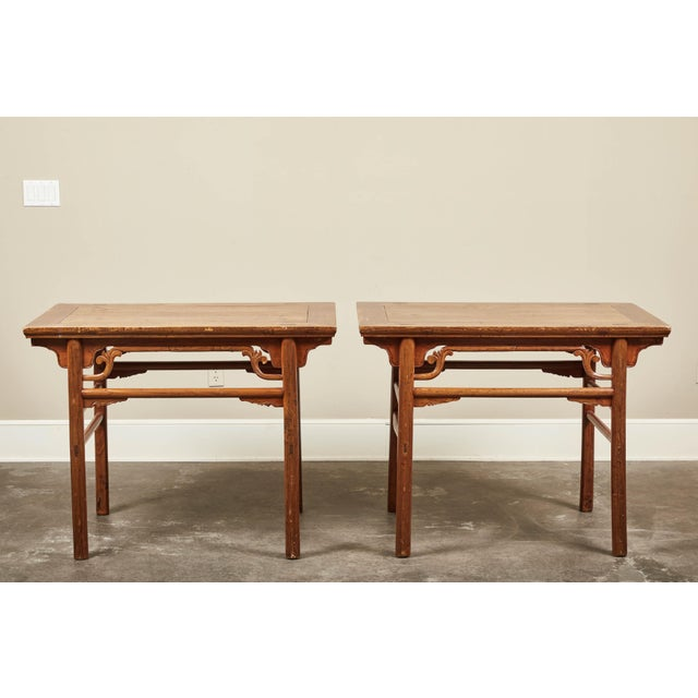 A pair of late 19th century Chinese elm altar side tables. Carved petite decoration below the frieze. Standing on rounded...