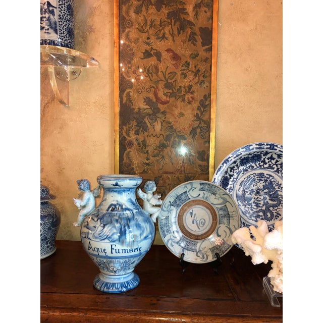 A 19th century Italian blue and white majolica urn with angle handles.