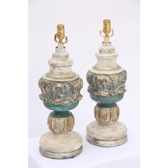 Pair of table lamps, painted and parcel-gilt, each urn-form body decorated with classical out-carving, raised on tiered...