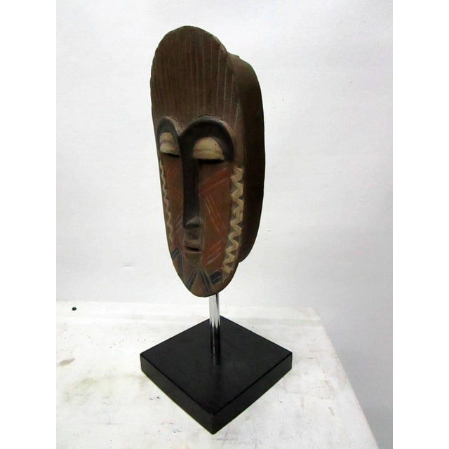 Oblong oval shaped African mask mounted on a black base. Mask is brown wood with tribal facial markings that could...