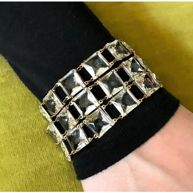 Definitely a statement piece, this dazzling three strand bracelet is made up of large, square clear faceted stones, prong...