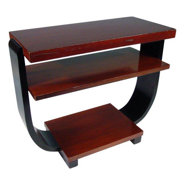 These elegant Art Deco side tables by Brown Saltman feature curved black lacquer sides bracketing three mahogany shelves.