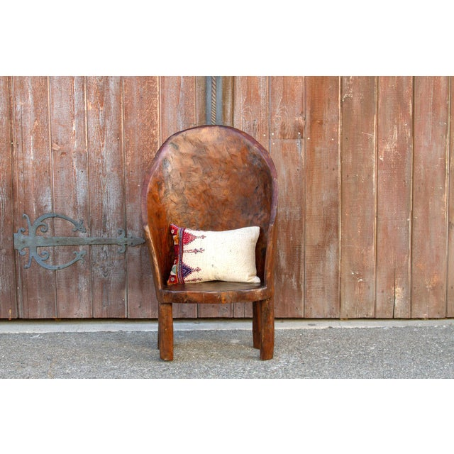 Rounded back primitive chair made in Nagaland, India. This chair is crafted from a single piece of teak wood using small...