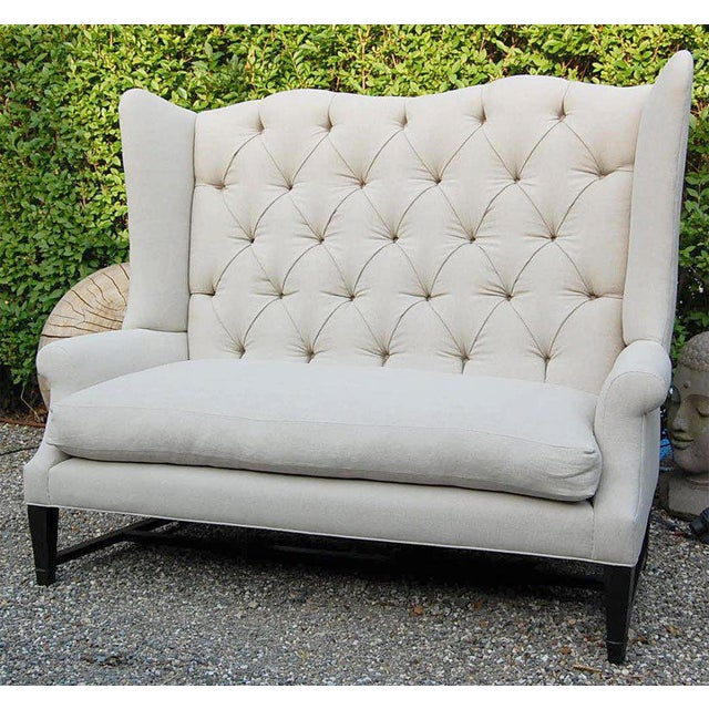 Monumental wing back sofa with and down seat on a stylized dark wood base with either a tufted or tight back... in natural...
