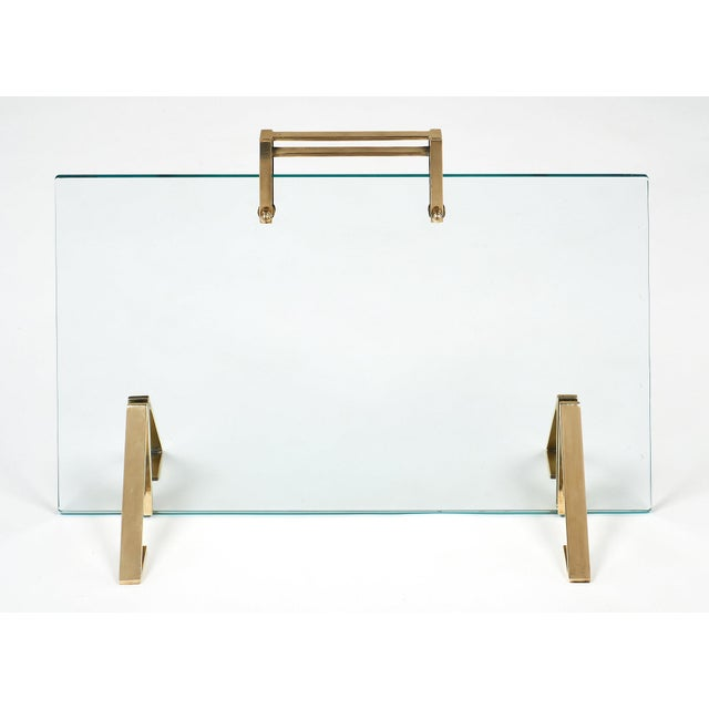 A rare, sleek fire screen attributed to iconic French designer, Jacques Adnet. The brass handle and supports contrast...