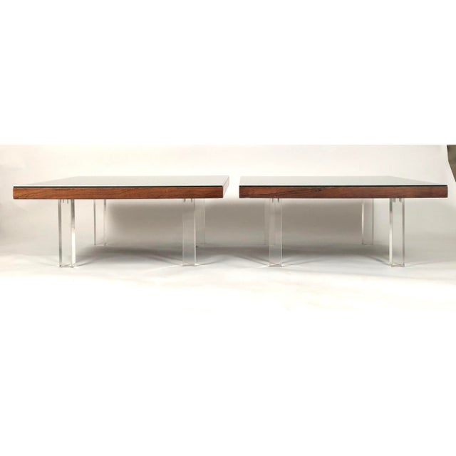 Two Milo Baughman rosewood and Lucite coffee tables, the square tops with richly figured book-matched rosewood veneer over...