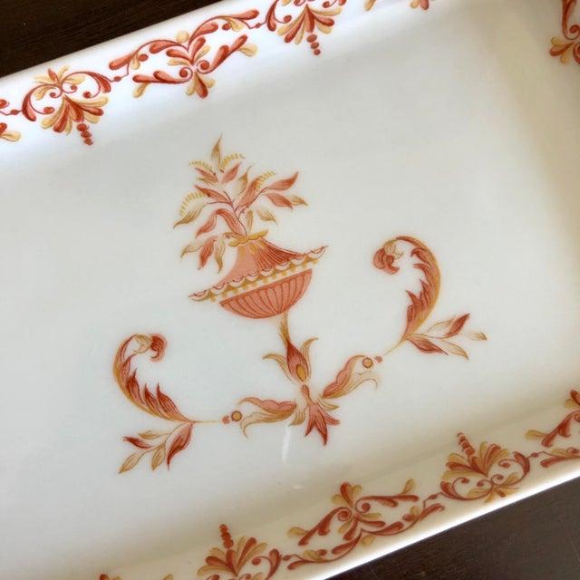 Antique French limoges porcelain trinket dish with red and orange flowering urn design.