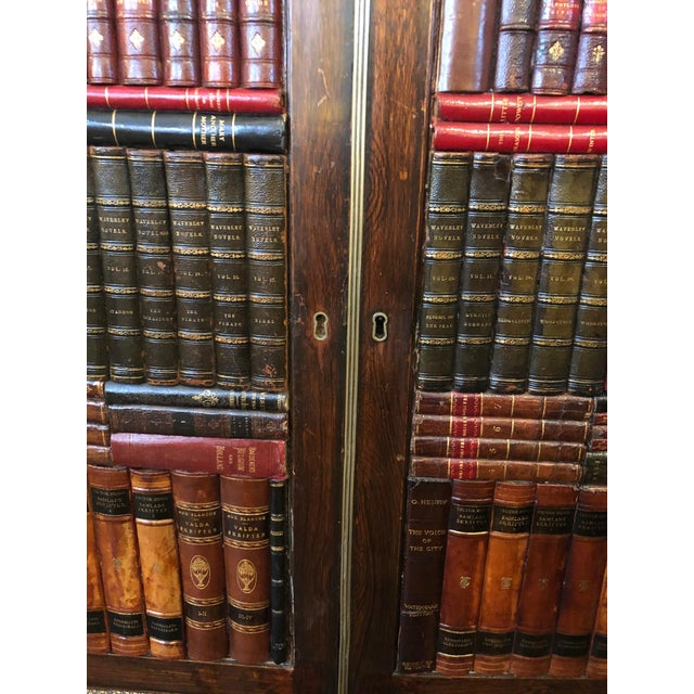 A gorgeous 19th century rosewood grain painted cabinet having two doors handsomely adorned with faux leather books and...