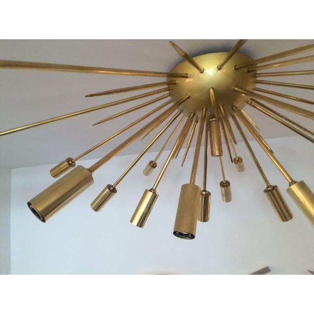 Iconic Sputnik as a ceiling flush mount fixture by Stilnovo. 19 polished brass light stems radiating from a matte brass...