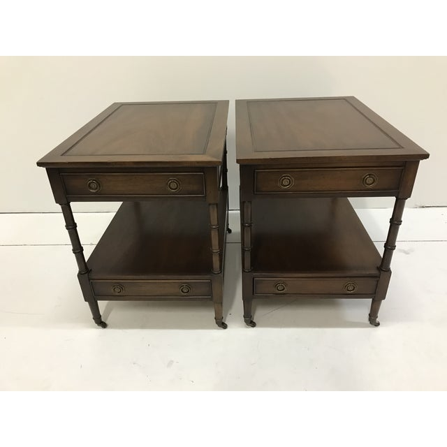 Pair of classic walnut Hekman side tables with faux carved bamboo legs atop brass cup on casters, model #322 Each has an...