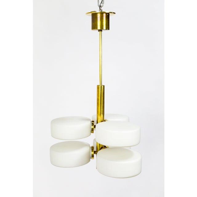 A rare Kaiser Leuchten sputnik pendant light with a sleek, polished brass stem and canopy, and 6 candelabra sockets with...