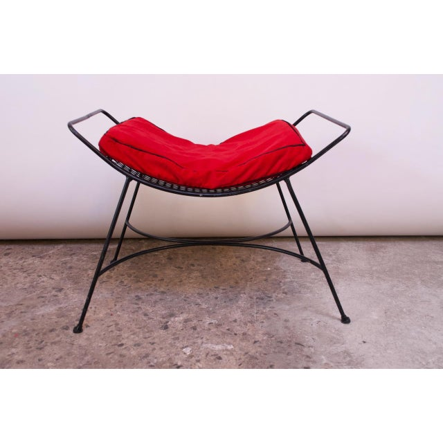 Circa 1950s wrought iron footstool / ottoman composed of a curved, mesh seat. Paired with a vintage cushion with age...