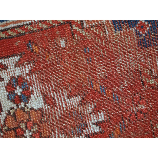 Handmade antique Caucasian runner in original distressed condition. The rug is in bright colours of red and blue. It has...