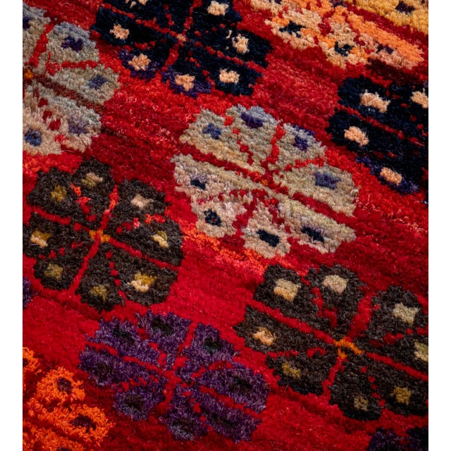 This vintage handwoven wool Turkish rug has a shaded tomato-red field with horizontal bands of polychrome stylized floral...